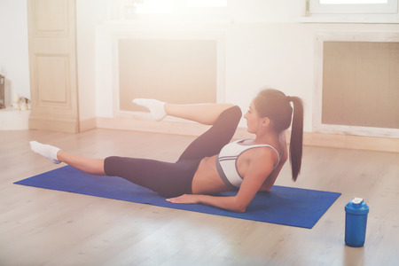 figure out: Young dark-haired athletic active sporty slim woman doing yoga exercise in the gym or home sitting on the floor.