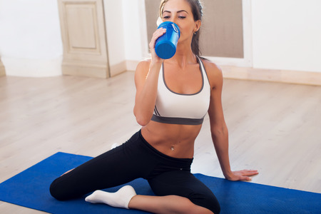 Beautiful athletic sporty woman sitting on yoga mat after some exercises drinks protein shake.