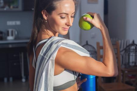 Mulher ativa atlético esportiva com a toalha no equipamento do esporte exploração maçã que mostra o bíceps estilo de vida saudável.