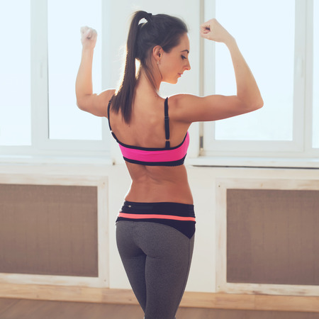 Active athletic sporty woman in sport outfit standing showing biceps muscles of the back and buttocks rear view healthy lifestyle. photo