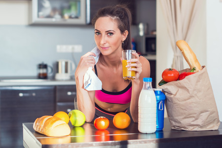 Pretty attractive athletic active sportive lady woman standing in kitchen with a towel on her shoulder and healthy food fresh fruits milk bread drinking juice.