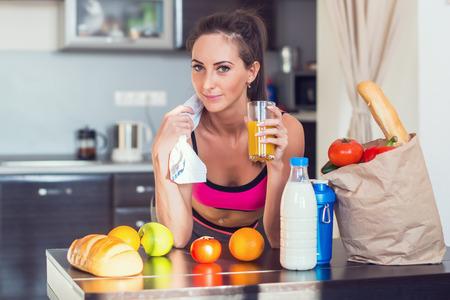 Vrij aantrekkelijke atletische actieve sportieve dame vrouw in de keuken met een handdoek op haar schouder en gezonde voeding vers fruit brood melk drinken sap.