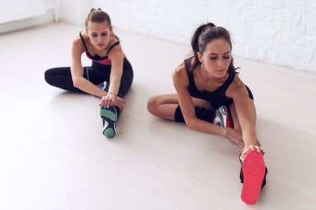 thigh: Group of fit women working stretching leg muscles of back to warm up at gym fitness, sport, training and lifestyle concept