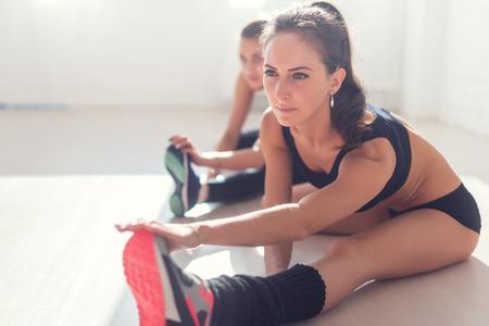 stretching: Grupo de mujeres del ajuste que estira los músculos de las piernas de nuevo a calentar en la aptitud del gimnasio, deporte, entrenamiento y estilo de vida concepto