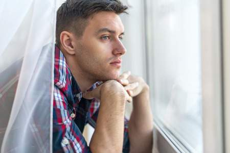 model male: Handsome pensive man guy watching through the window concept sadness sorrow pain waiting.