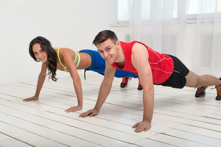 push ups: Training. Beautiful girl and handsome guy workout together making push ups on the white wooden floor. Stock Photo