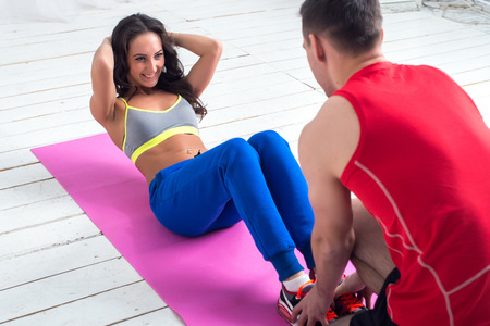 woman exercising: athletic sporty couple friends. Woman doing crunches abdominal exercises on floor in gym with a help of guy concept training exercising workout fitness aerobic.