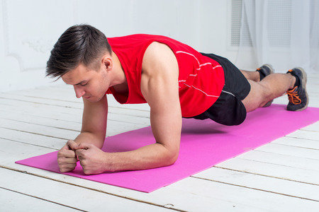 plank: fitness training athletic sporty man doing plank exercise in gym or home concept exercising workout aerobic. Stock Photo