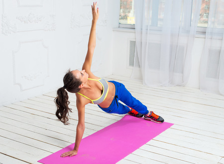Active sportive woman doing handstand exercise practicing the side plank pose during yoga class in a gym photo