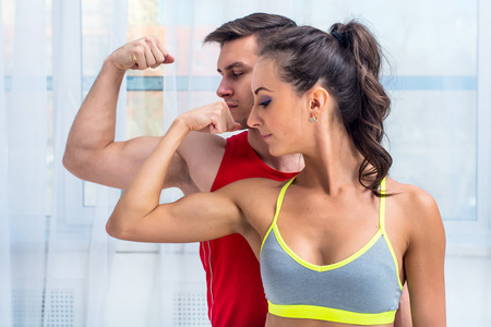 protein: Active athletic sportive woman girl and man showing their muscles biceps healthy lifestyle.