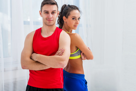 sport hall: sporty couple friends slim athletic ambitious woman and confident man trainers team or coach client in sport hall gym standing arms crossed sportsmen professionals looking at camera.