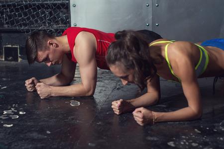 fitnes: pasuje sportowy człowieka i kobieta robi rdzenia deski ćwiczenia fizyczne z powrotem i moc mięśni prasowe Koncepcja siłownia sport sportowiec CrossFit Fitness trening siła. Zdjęcie Seryjne