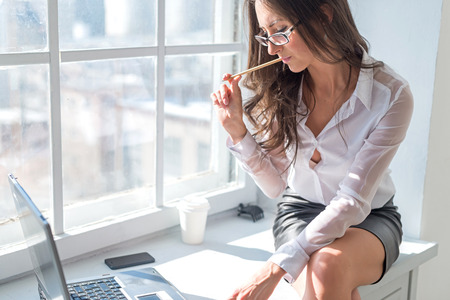 secretary skirt: businesswoman sitting next to the window in front the laptop notebook with the pencil in office. Stock Photo