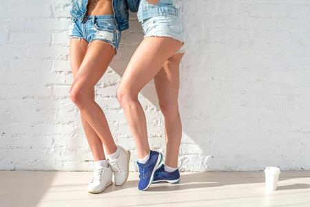 desportivo longas pernas sexy de duas belas mulheres shorts jeans moda casual street style dia ensolarado urbano que está próximo à parede.