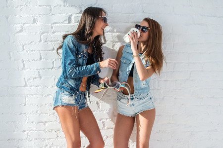 jeanswear: two pretty girls wearing sunglasses in summer jeanswear street urban casual style talking, laughing having fun on the background of brick wall