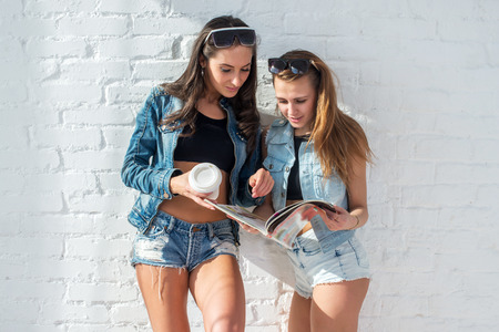 Two beautiful girls friends reading the magazine wearing sunglasses and denim jeans jackets and shorts urban street casual style. photo