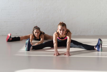 to bend: Two young women stretching seated wide legged forward bend in the gym.