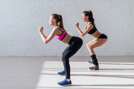 squat: Tough stamina training for two young stunning fitness models doing squats together indoors. Stock Photo