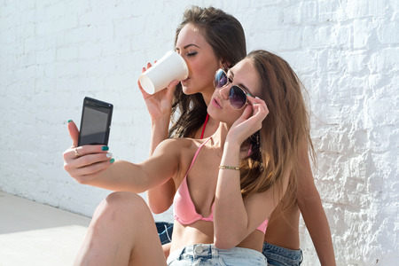 Female friends drinking coffee taking self-portrait picture photos with mobile smart phone or pocket camera on vacation wearing bikini bra swimsuit summer sunny day street urban casual style. photo