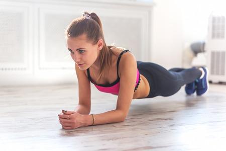 nutrici�n: Fitnes Slim joven con coleta haciendo ejercicio de tablones en el interior en la gimnasia en casa. Foto de archivo