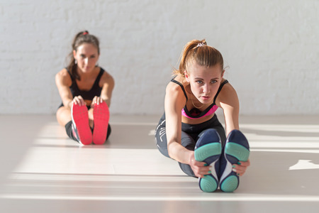 mujeres sentadas: Dos mujeres jóvenes sentados estiramiento se inclina hacia adelante en calor en la aptitud del gimnasio, deporte, entrenamiento y estilo de vida concepto. Foto de archivo