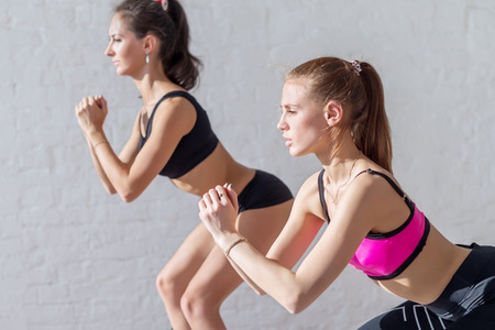 squats: two girls doing squats together indoors training warm up at gym fitness, sport and lifestyle concept.