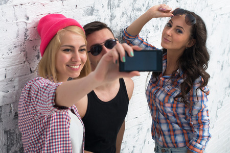 jeanswear: two women and man friends taking selfie together wearing summer clothes  jeans shorts jeanswear street urban casual style having fun Stock Photo