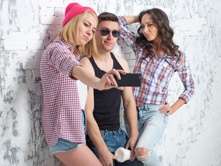 jeanswear: two women and man friends taking selfie together wearing summer clothes  jeans shorts jeanswear street urban casual style having fun Archivio Fotografico
