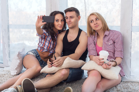 jeanswear: two girls and guy friends taking selfie together wearing summer clothes  jeans shorts jeanswear street urban casual style having fun at home. Stock Photo