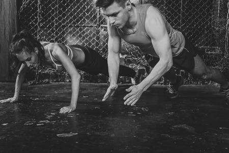 atleta: Deportistas. Hombre apto del entrenador masculino y mujer haciendo palmas flexiones fuerza explosiva de energ�a concepto de entrenamiento f�sico crossfit entrenamiento fuerza.