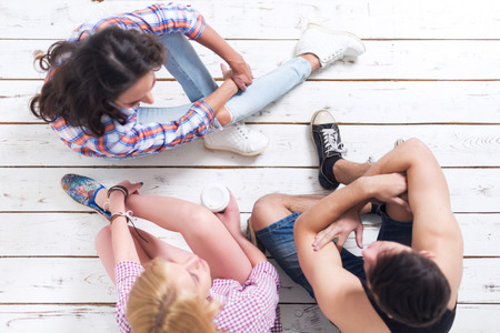 jeanswear: Friends two girls and guy sitting on floor in summer jeanswear street urban casual style talking, having fun, top view. Stock Photo