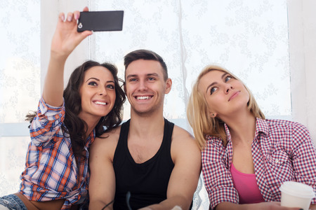 jeanswear: Happy friends two women and man taking selfie with camera or smartphone together wearing summer clothes  jeans shorts jeanswear street urban casual style having fun