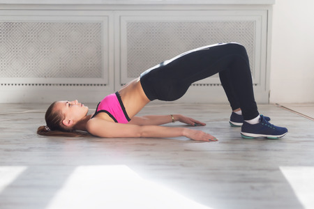 Side view of young woman doing gymnastics the half bridge pose in fitness studio or home practices yoga warming up exercises for spine, backbend, strengthening back and shoulders muscles. Archivio Fotografico