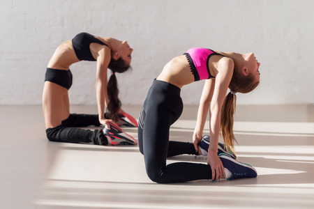 arching: women warming up arching stretching their backs holding legs and working out in a gym yoga class. Stock Photo