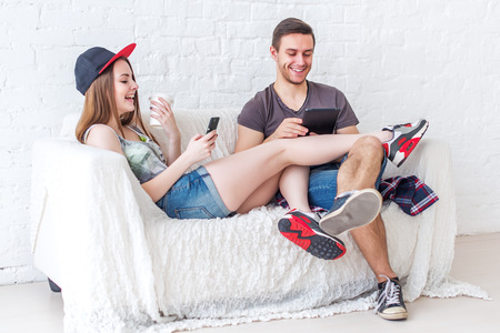 Young friends funny guys active people have fun together sitting on sofa send message chatting using app gaming with their smartphones at home concept social media.