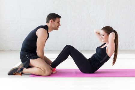 laying abs exercise: woman doing abdominal crunches press exercise on the mat with her sports male trainer in gym concept sport, fitness, lifestyle and people. Stock Photo