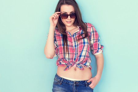 Outdoor summer closeup portrait of young stylish fashion glamorous woman in shirt and denim shorts sunglasses standing on the blue background.