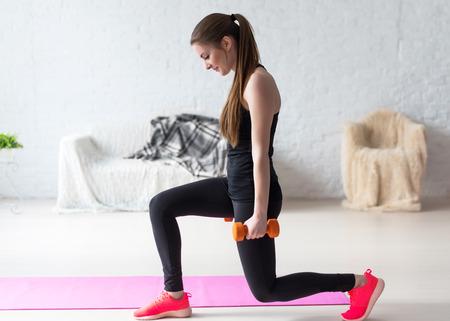 haciendo ejercicio: Mujer atlética calentamiento hace estocadas con mancuernas ejercicio de entrenamiento para las piernas a tope en casa estilo de vida saludable concepto culturismo deporte ponderado. Foto de archivo