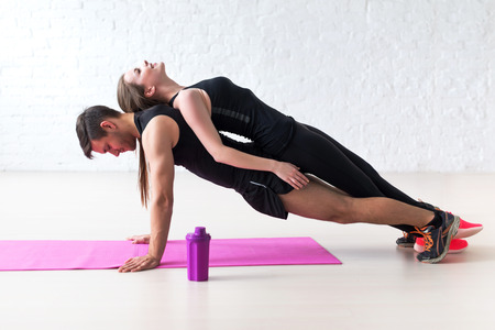 musculine: man doing push ups with woman laying on back at gym or home concept fitness sport training teamwork and lifestyle