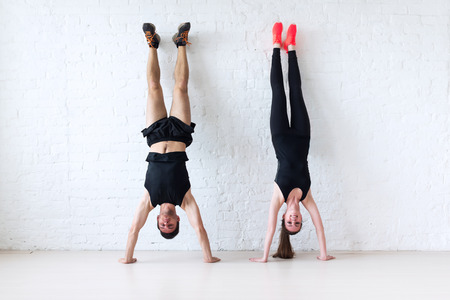gym girl: sportsmen woman and man doing a handstand against wall concept balance sport fitness lifestyle and people.