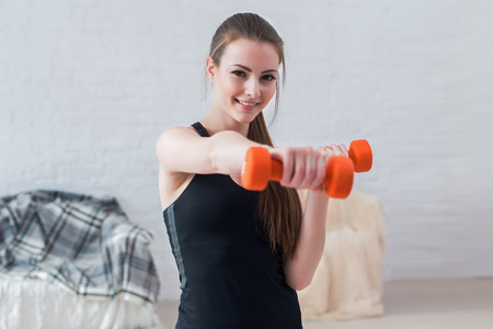 Active sportive athletic woman boxing dumbbells pumping up muscles towards camera in bright room concept fitness sport training lifestyle. Imagens
