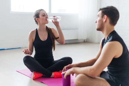 conversing: Sport connecting people friends relaxing after workout girl drinking water and man Side view of young couple in sports clothing sitting face to face and talking conversing
