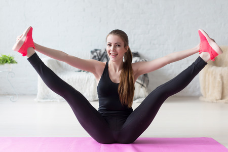 stretches: Funny smiling girl holding legs apart doing exercises aerobics warming up with gymnastics for flexibility leg stretching workout at home fitness Stock Photo
