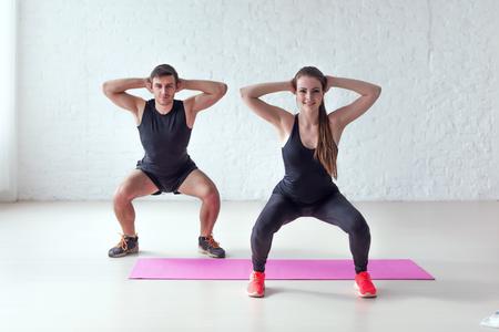 Fitness man en vrouw te oefenen squat oefening handen achter het hoofd concept van sport, training, warming-up en lifestyle.