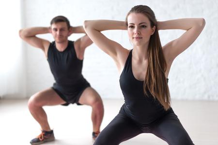 ejercicio aer�bico: Gimnasio hombre y la mujer el ejercicio de sentadilla ejercicio las manos detr�s de la cabeza concepto deporte, entrenamiento, calentamiento y estilo de vida. Foto de archivo