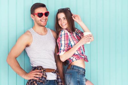 romance: Par de amigos felices con gafas de sol divertidas forma de corazón en la calle jeanswear verano estilo casual urbano hablando divertirse bebiendo café de pie cerca de la pared
