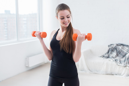 Active sportive athletic woman with dumbbells pumping up muscles biceps concept fitness sport training lifestyle Stockfoto
