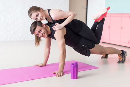 musculine: man doing push ups with woman laying on back at gym or home smiling looking at camera concept fitness sport training teamwork and lifestyle.