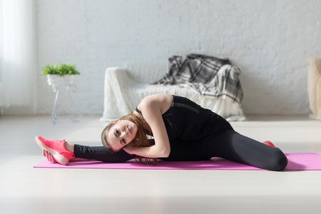 gymnastics: Fit woman Hoch Körper Flexibilität streckte ihre Beine und Rücken, um sich aufzuwärmen tun Aerobic Gymnastik-Übungen zu Hause. Lizenzfreie Bilder