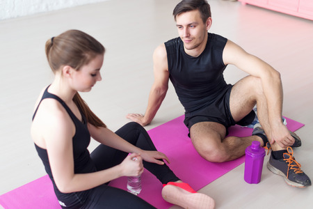conversing: Sport connecting people friends relaxing after workout girl drinking water and man. Young couple in sports clothing sitting talking conversing Stock Photo